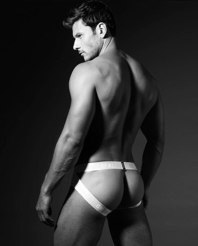 The contrast from the wide strapped jock and his white round ass is cock stirring